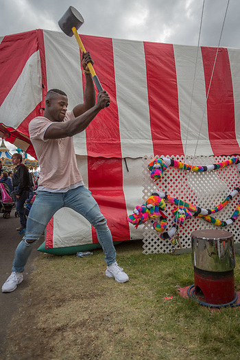"U.S. Army Private Reuben Geimah test his strength at the ""Hig Striker"" on the midway at the Alaska State Fair in Palmer, Alaska (Clark James Mishler)"