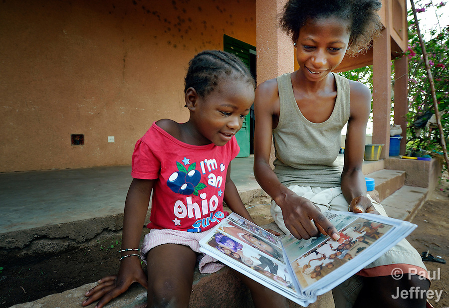 Three-year old Naomi Wallet Tafaki and her 21-year old sister Monique Kone look at an album of family photographs in a Catholic training center in Niamana, Mali. Several families displaced by the fighting in northern Mali took refuge in the center, and have received support from the ACT Alliance. (Paul Jeffrey)