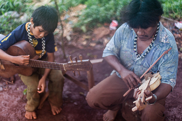 Angel Morinigo, an Mbya Guarani craftsman and musician from Andresito village near San Ignacio, Misiones, Argentina, playing traditional Guarani folk music with his son. (Jason Rothe)