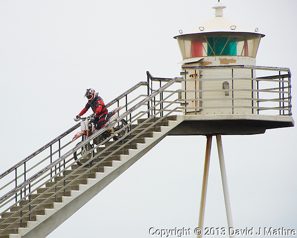 Motocross Rider Descending the Stairway of the Urða Lighthouse. Located on a lava field on the eastern point of Heimaey in Vestmannaeyjar, Iceland. Image taken with a Nikon 1 V2 camera and 10-100 mm VR lens (ISO 160, 100 mm, f/5.6, 1/500 sec). Nikonians Academy Photo Workshop. (David J Mathre)