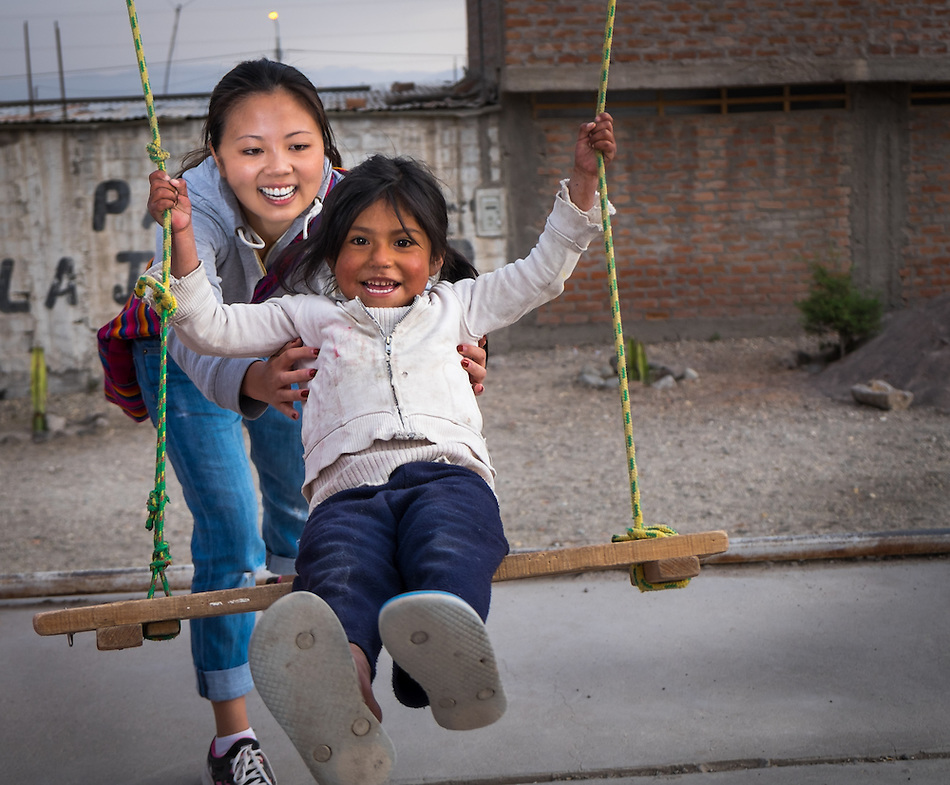AREQUIPA, PERU - APRIL 3, 2014: Volunteer playing with kid in the community of Flora Tristan for HOOP Peru. HOOP Peru is a NGO fully committed to breaking the cycle of poverty by empowering the Flora Tristan families through enhancing their education. (Daniel Korzeniewski)