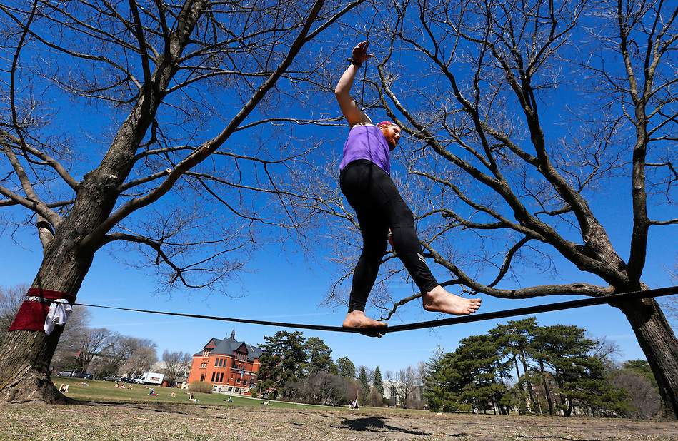 Iowa State junior Austin Renes of Carmel, Iowa walks a slackline between a pair of trees on central campus on Wednesday, April 1, 2015. (Photo by Christopher Gannon) (Christopher Gannon)