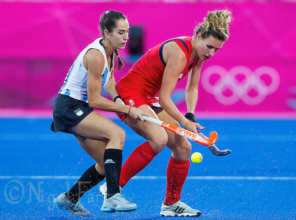 08 AUG 2012 - LONDON, GBR - Ashleigh Ball (GBR) of Great Britain (right) tries to win the ball from Josefina Sruoga (ARG) of Argentina (left) during the two teams London 2012 Olympic Games women's semi final match at the Riverbank Arena in the Olympic Park, Stratford, London, Great Britain (PHOTO (C) 2012 NIGEL FARROW) (NIGEL FARROW/(C) 2012 NIGEL FARROW)