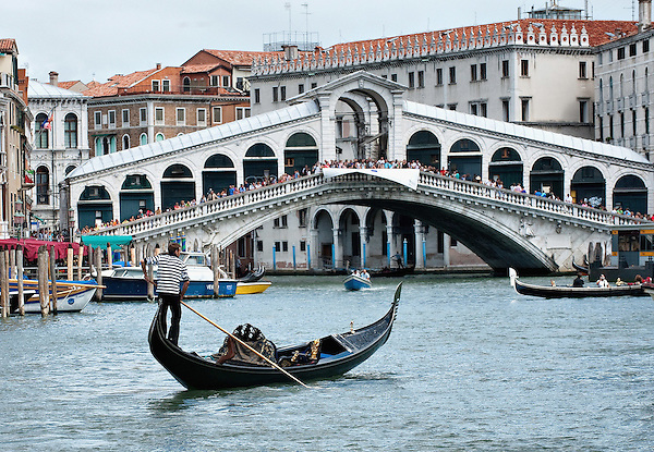 VENICE, ITALY - AUGUST 11:  A Gondola sails the Grand Canal in front of a busy Rialto bridge on August 11, 2011 in Venice, Italy. Italian heritage group Italia Nostra warned  that Venice is facing an irreversible environmental catastrophe unless visitor numbers are capped. The acceptable maximum number of tourists for Venice is 33,000. In 2011 the average number of visitors to the city daily is 60,000 that is too high for such a fragile city and is causing the gradual destruction of the lagoon ecosystem. (Marco Secchi)