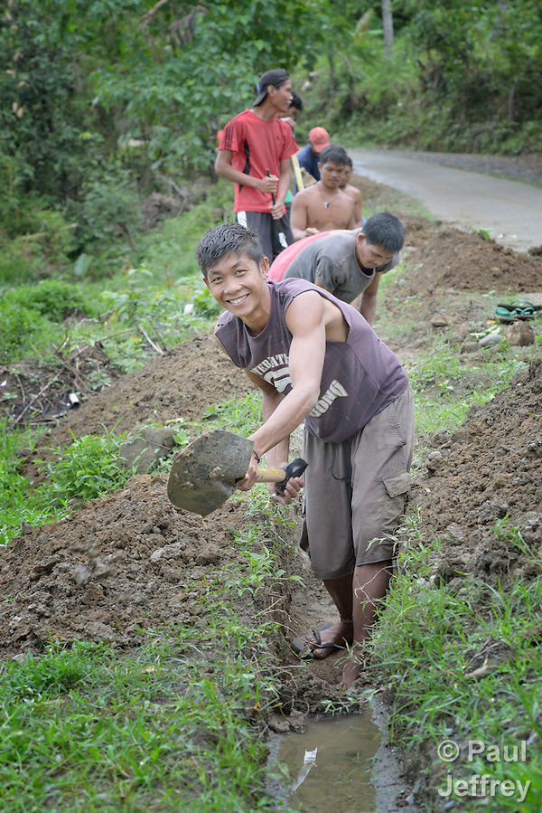 Jaime Papiyona digs a ditch for a water pipe as part of a cash for work program in the village of Cambayan in the Philippines province of Samar. The region was hit hard by Typhoon Haiyan in November 2013. Known locally as Yolanda, the storm left much of the community's infrastructure a shambles. Norwegian Church Aid, a member of the ACT Alliance, is helping the community rehabilitate its potable water system as well as build new toilets. (Paul Jeffrey)