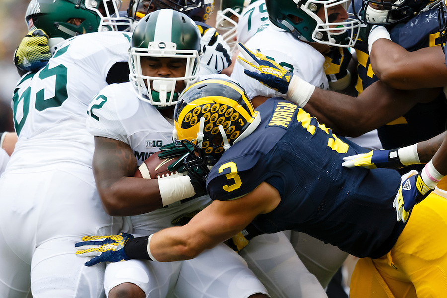Oct 17, 2015; Ann Arbor, MI, USA; Michigan State Spartans running back Delton Williams (22) attempts to run the ball Michigan Wolverines linebacker Desmond Morgan (3) moves in to tackle in the first quarter at Michigan Stadium. Mandatory Credit: Rick Osentoski-USA TODAY Sports (Rick Osentoski/Rick Osentoski-USA TODAY Sports)