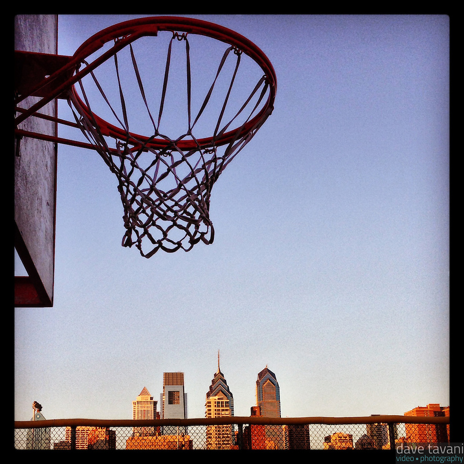 A basketball hoop looms above the city skyline at the Marian Anderson Recreation Center just before dusk in south Philadelphia, February 9, 2013. (Dave Tavani)