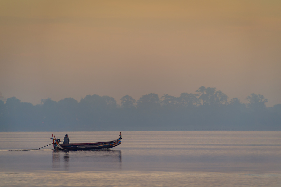 MANDALAY, MYANMAR - CIRCA DECEMBER 2013:  Typical boat crossing the Taungthaman Lake early morning near Mandalay (Daniel Korzeniewski)