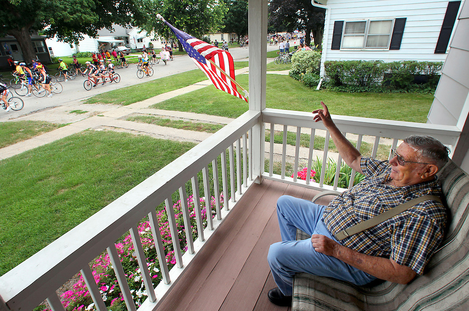 """Bud Allan, 81, takes in the parade of RAGBRAI riders flowing down Main Street in Baxter on July 28 along RAGBRAI XXXIX.  """"I just can't hardly believe it,"""" he said of the crush of riders hitting town. (Christopher Gannon/The Register)"""