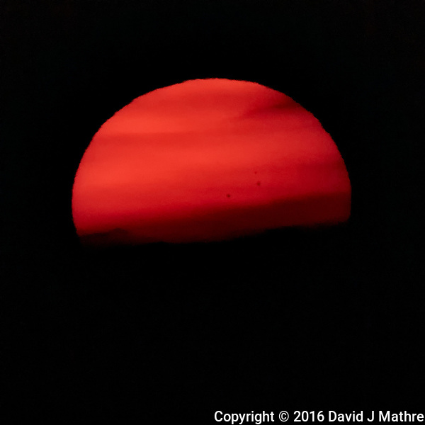 Premature Sunset through low clouds on the horizon. Check out the sunspots. Image taken with a Nikon 1 V3 camera and 70-300 mm VR lens (ISO 200, 300 mm, f/8, 1/500 sec). (David J Mathre)