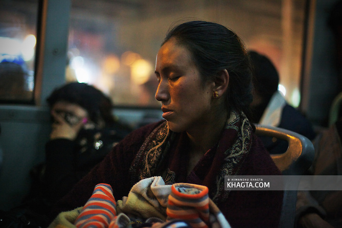 A tired lady from Ladakh, takes a short nap in the bus in New Delhi. The flight got diverted and the family couldn't reach Leh. (Himanshu Khagta)