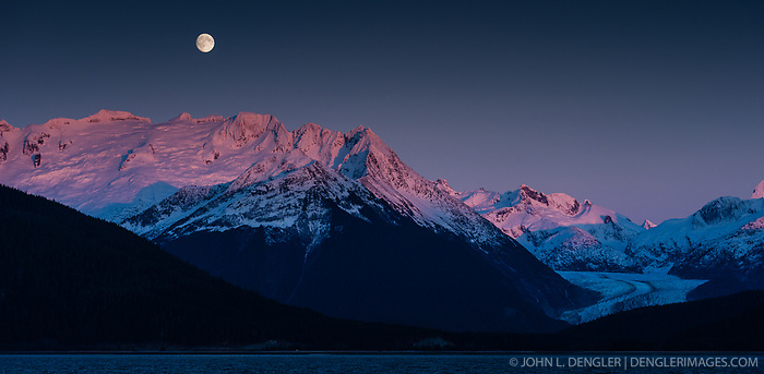 A full moon rises above Mount Ernest Gruering and the Herbert Glacier near Juneau, Alaska as the final rays of the sun at sunset baths mountain tops in alpenglow light. The view is from the Alaska Marine Highway System ferry FVF Fairweather as it traveled down the Lynn Canal from Haines. (John L. Dengler)
