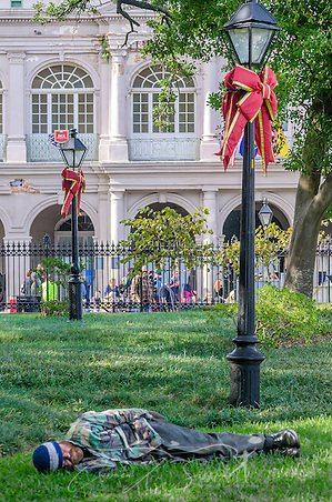 Homeless man sleeping in New Orleans Jackson Square