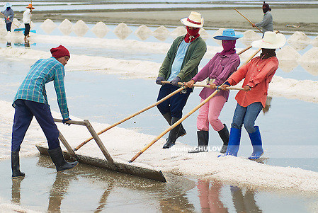 HUAHIN, THAILAND - MAY 13, 2008: Unidentified people work at the salt farm in Huahin, Thailand. Salt production is one of the main industries in Huahin area, it brings modest income to many local families. (Dmitry Chulov)