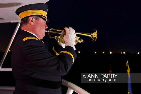 Freeport, New York, USA. 10th Sept. 2014. A bugler plays taps at night on board the boat Miss Freeport V, which sailed from the Woodcleft Canal of the Freeport Nautical Mile after a dockside remembrance ceremony in honor of victims of the terrorist attacks of September 11 2001. American Legion, Patriot Guard Riders, and Captain Frank Rizzo hosted the ceremonies on the eve of the 13th anniversary of the 9/11 attacks. (Ann Parry/Ann Parry, ann-parry.com)