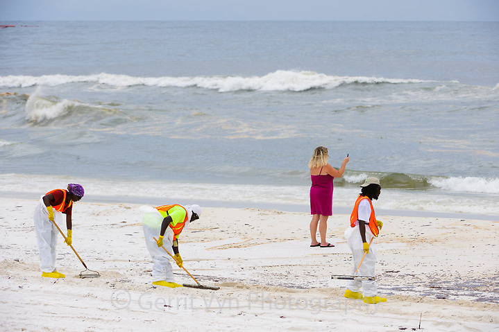 A lady taking a cell phone picture as oil rolls in and beach cleaners. Orange Beach, Baldwin County, Alabama. June. (Gerrit Vyn)