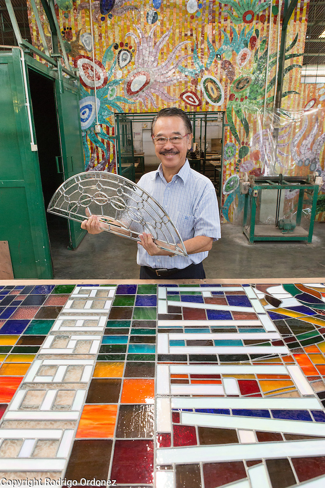 Eztu Glass founder and CEO Brian Yaputra poses for a portrait holding a small stained glass window at his company's factory in Tangerang, near Jakarta, Indonesia, on July 2, 2015. (Rodrigo Ordonez)