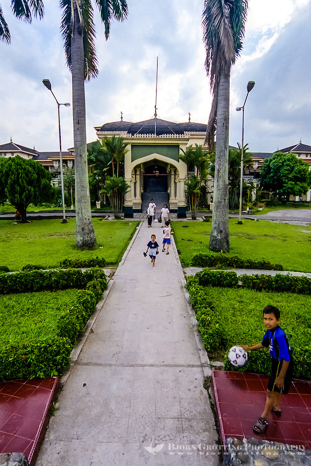 Indonesia, Sumatra. Medan. Istana Maimun Palace was built in 1888 by the sultan of Deli. His ancestors still occupy one wing of the building. Children playing outside the palace. (Photo Bjorn Grotting)