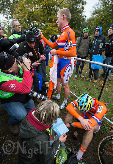 03 NOV 2012 - IPSWICH, GBR - Mike Teunissen (NED) (top centre in orange) of the Netherlands talks with friends after winning the Under 23 Men's European Cyclo-Cross Championships in Chantry Park, Ipswich, Suffolk, Great Britain as his team mate silver medalist Corne van Kessel (NED) (bottom right) recovers .(PHOTO (C) 2012 NIGEL FARROW) (NIGEL FARROW/(C) 2012 NIGEL FARROW)