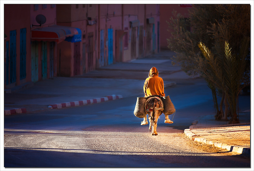 Man on donkey rides early morning on a road in Tinghir, Morocco. (Rosa Frei)
