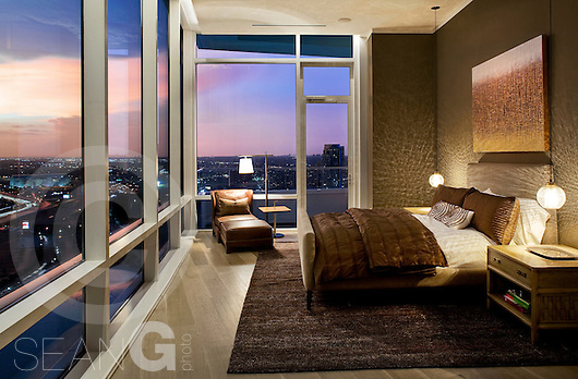 Bedroom of a Luxury high-rise condominium overlooks city and a colorful sunset (Sean Gallagher/Sean Gallagher Photography)