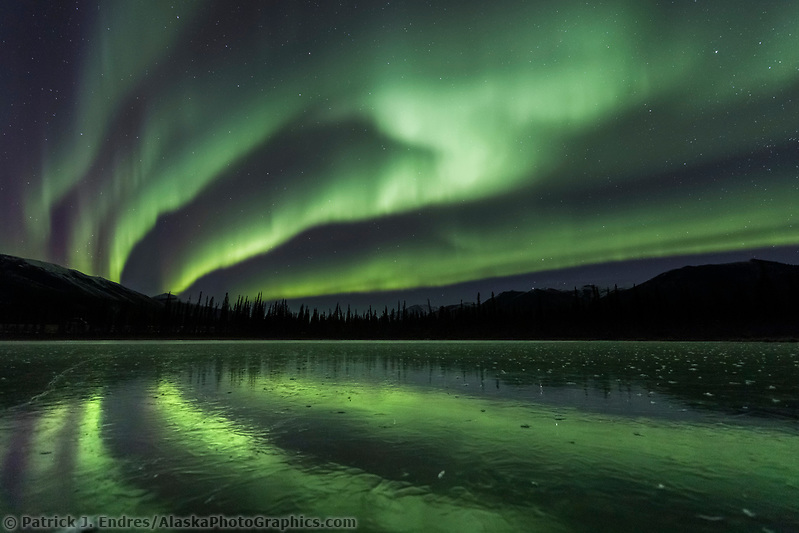 Aurora borealis reflects on a frozen lake in the Brooks Range mountains, Arctic, Alaska. (Patrick J Endres / AlaskaPhotoGraphics.com)