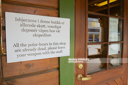 LONGYEARBYEN, NORWAY - SEPTEMBER 01, 2011: Information sign at the entrance to the souvenir shop in Norwegian and English instructing not to enter with weapons in Longyearbyen, Norway. (Dmitry Chulov)