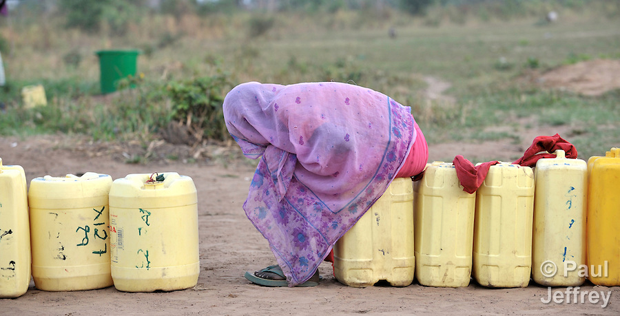 A woman waits in line at a well in Yei, Southern Sudan, provided by the United Methodist Committee on Relief (UMCOR).