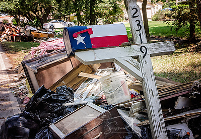 A mailbox featuring a Texas flag motif tilts over a pile of flood debris following Hurricane Harvey, Sept. 6, 2017, in Houston, Texas. The storm dumped nearly 52 inches of rain on Houston, resulting in heavy flooding. The flood was the third this neighborhood has experienced, and most residents' belongings were not salvageable. (Photo by Carmen K. Sisson/Cloudybright) (Carmen K. Sisson/Cloudybright)