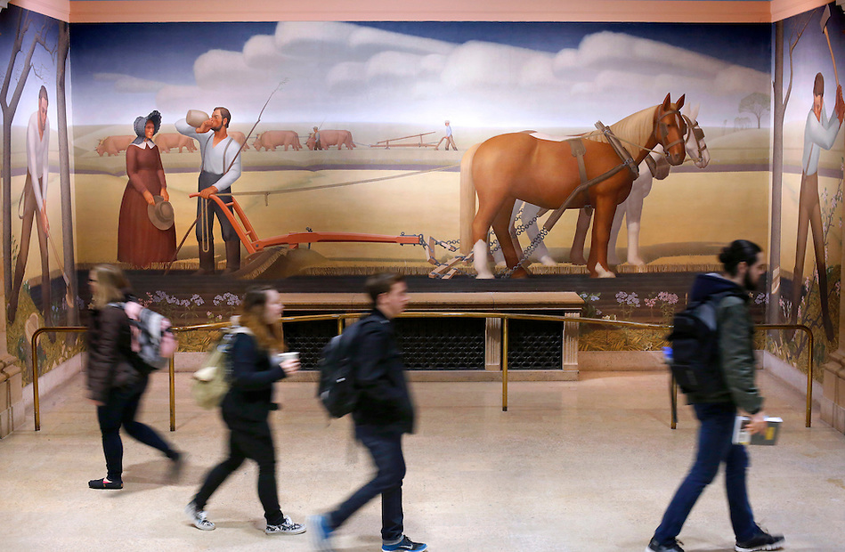 "Students pass Grant Wood's ""When Tillage Begins"" inside Parks Library on Monday, February 16, 2015. The three-panel mural portrays the beginning of tillage in Iowa by the pioneers in the 1840s. (Photo by Christopher Gannon) (Christopher Gannon)"
