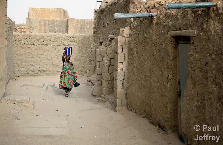 Carrying water on her head, a woman walks along a street in Timbuktu, the northern Mali city that was seized by Islamist fighters in 2012 and then liberated by French and Malian soldiers in early 2013. During jihadist rule, women and girls were not permitted in public unless they were completely covered. (Paul Jeffrey)