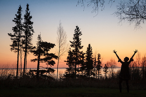 Ellen Arvold impersonates a tree as she celebrates a beautiful fall sunset over Turnagain Arm  in South Anchorage. (Clark James Mishler)