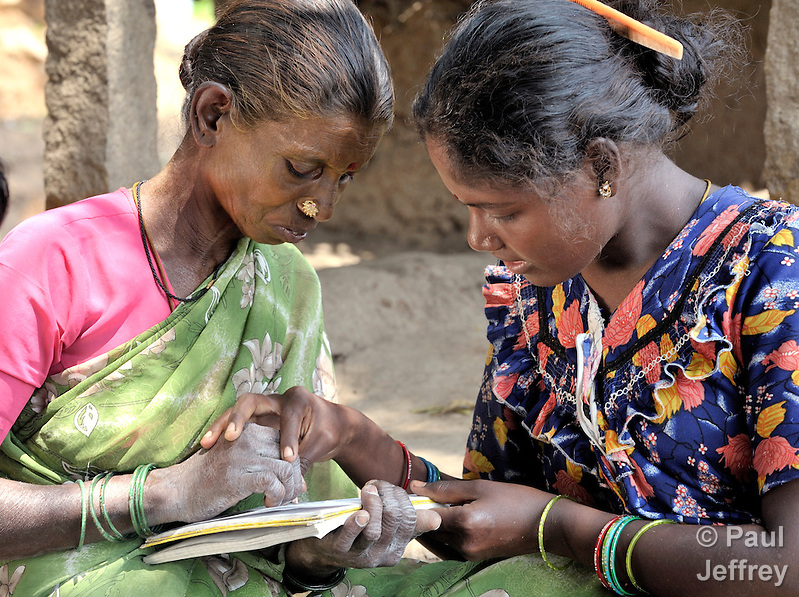 Angali (right) helps Kaniamma with writing during a women's literacy class in Nandambakkam, a tribal village in the southern India state of Tamil Nadu. (Paul Jeffrey)