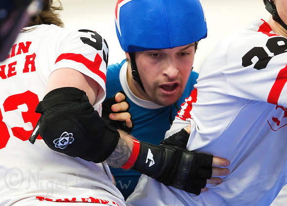 16 MAR 2014 - BIRMINGHAM, GBR - Team France jammer The Cleaner (centre) tries to force his way between Team England blockers Rollin Stone R and Flat Track Bully during the inaugural Men's Roller Derby World Cup at the Futsal Arena in Birmingham, West Midlands, Great Britain (PHOTO COPYRIGHT © 2014 NIGEL FARROW, ALL RIGHTS RESERVED) (NIGEL FARROW/COPYRIGHT © 2014 NIGEL FARROW : www.nigelfarrow.com)