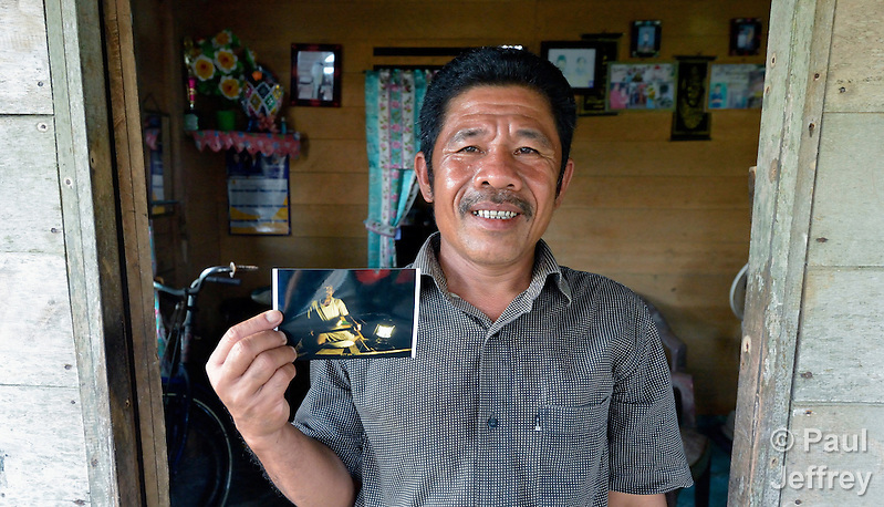 In 2014, Nurul Huda holds a photo of him fishing at night in 2007 off the Indonesian island of Nias. Huda, a resident of the seaside village of Olora, survived a giant March 2005 earthquake on Nias, yet lost much of his fishing equipment. Church World Service, a member of the ACT Alliance, provided new nets and boats for the fishers of Olora, allowing them to restart their lives. Yet fish have grown scarce in recent years, while fuel prices have risen, making it harder for fishers to earn a living. Huda no longer can afford a motor, and so fishes closer to the island, where the fish are smaller. Climate change has also made it more difficult to predict fish movements, and changing weather patterns can surprise the fishermen at sea. Huda, not surprisingly, wonders if his 16-year old son should pursue another line of work. (Paul Jeffrey)