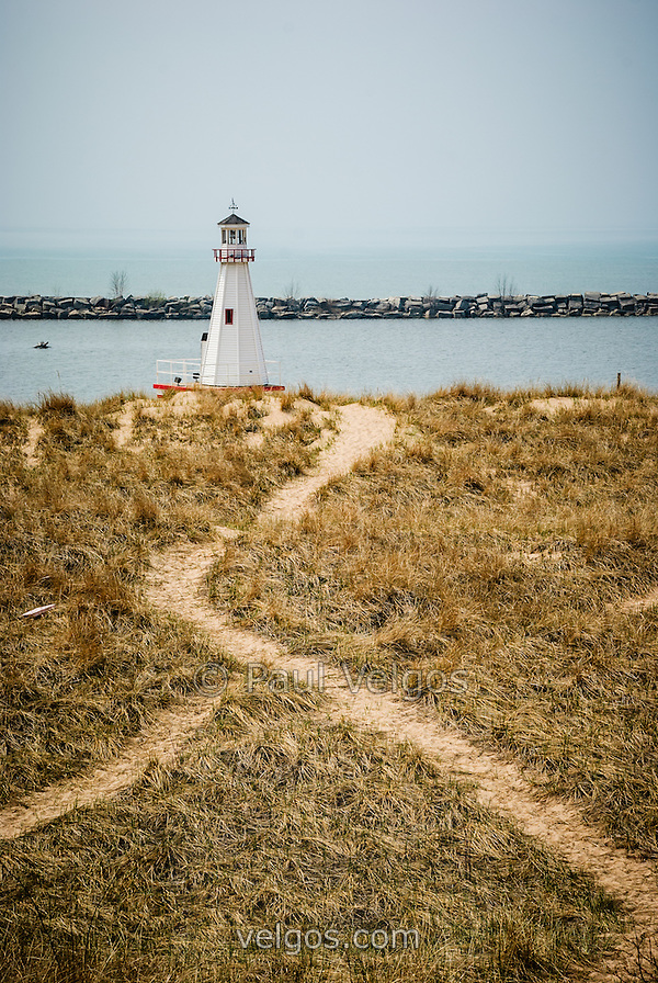 Photo of the lighthouse in New Buffalo Michigan with a sandy grass trail and jetty rock breakwall in the background. (Paul Velgos)