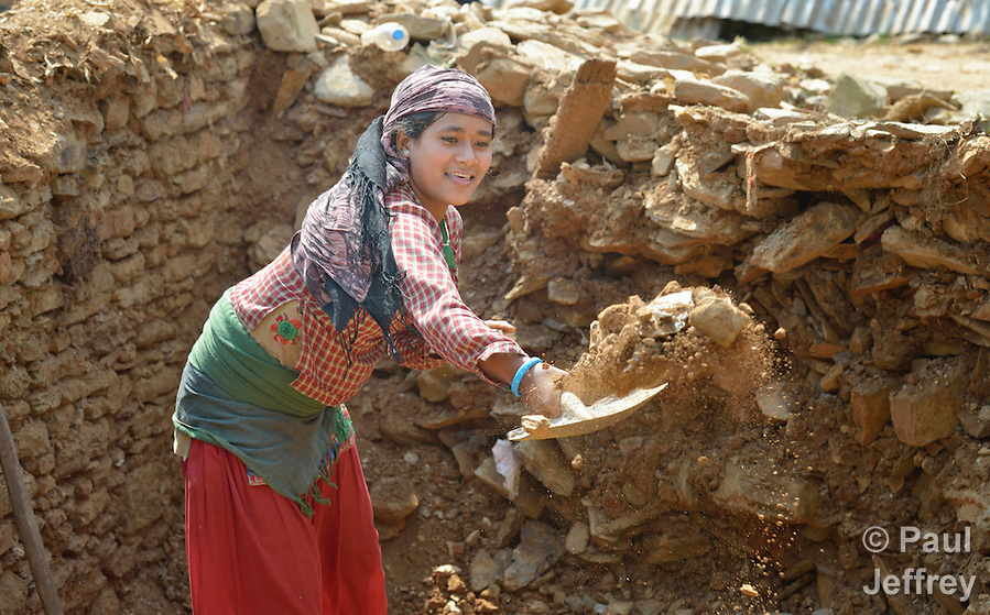 Anita Shakya cleans up rubble in Dhawa, a village in the Gorkha District of Nepal. (Paul Jeffrey)
