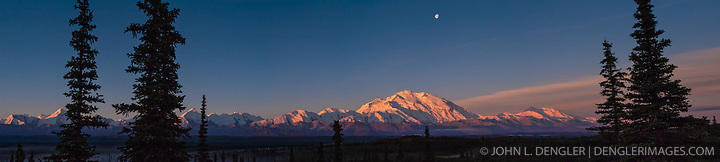 Sun rises on Mount McKinley and the Alaska Range as seen from Wonder Lake in Denali National Park and Preserve in Alaska. Also pictured is the setting moon, above Mount McKinley. Mount McKinley also known as Denali is North America's tallest peak at 20,320 feet and towers over 18,000 feet above the surrounding lowlands. Other mountain peaks pictured include: Mount Brooks, Mount Silverthrone, Mount Tatum, Mount Carpe and Mount Foraker. SPECIAL NOTE: This image is a panorama composite consisting of multiple overlapping images stitched together. (John L. Dengler)