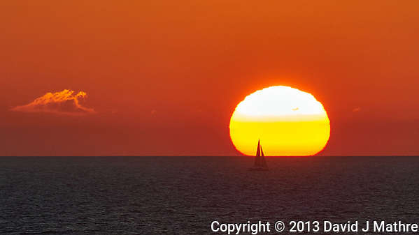 Silhouette of a Sailboat Passing in Front of the Sun at Sunset from the Deck of the MV Explorer. Crossing the Baltic Sea from Stockholm to Copenhagen. Image taken with a Nikon D4 camera and 80-400 mm VRII lens (ISO 400, 400 mm, f/11, 1/500 sec). (David J Mathre)