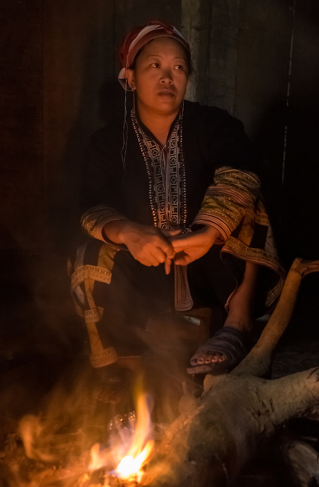 SAPA, VIETNAM - CIRCA SEPTEMBER 2014:  Woman from the Red Dao minority with fire pit inside a home in Ta Phin Village near Sapa, north Vietnam. (Daniel Korzeniewski)