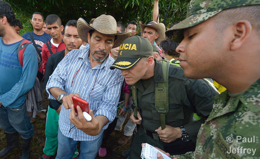 A protestor shows a police official images on his camera phone of police and soldiers mistreating demonstrators along a highway in Barrancabermeja, Colombia, where hundreds of people maintained a presence protesting government policies. The protest was part of a nationwide agrarian strike which at times closed major roads in the war-torn South American country. (Paul Jeffrey)