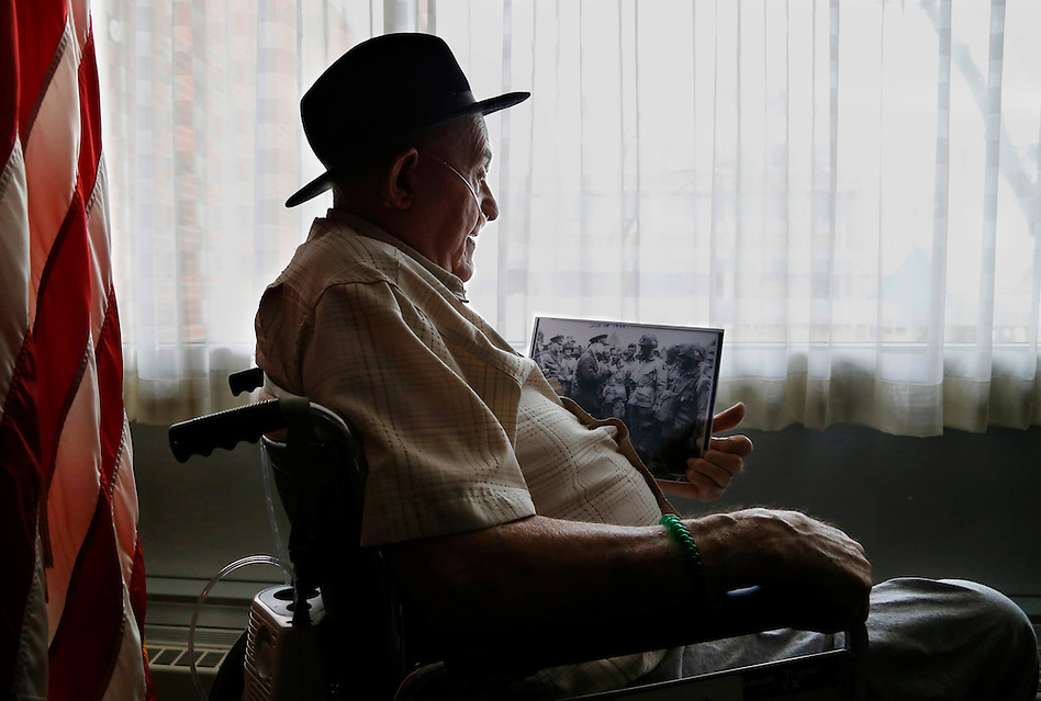 "Fred Lindsey, 92, of Marshalltown, Iowa looks at an historic image of Gen. Dwight Eisenhower visiting with soldiers days before the Normandy invasion during World War II.  Lindsey is in the photo, at left in the background.  He was a 22-year-old First Sergeant from Sioux City, Iowa at the time.  Seeing Eisenhower that day, June 4, 1944, ""was good medicine,"" Lindsey says. (Christopher Gannon/The Register)"
