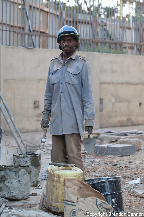 A mason at work in Nairobi, Kenya. He is part of a construction crew working to finish an expansion of The Junction shopping center in Nairobi, Kenya. (Photographer: Brendan Bannon)