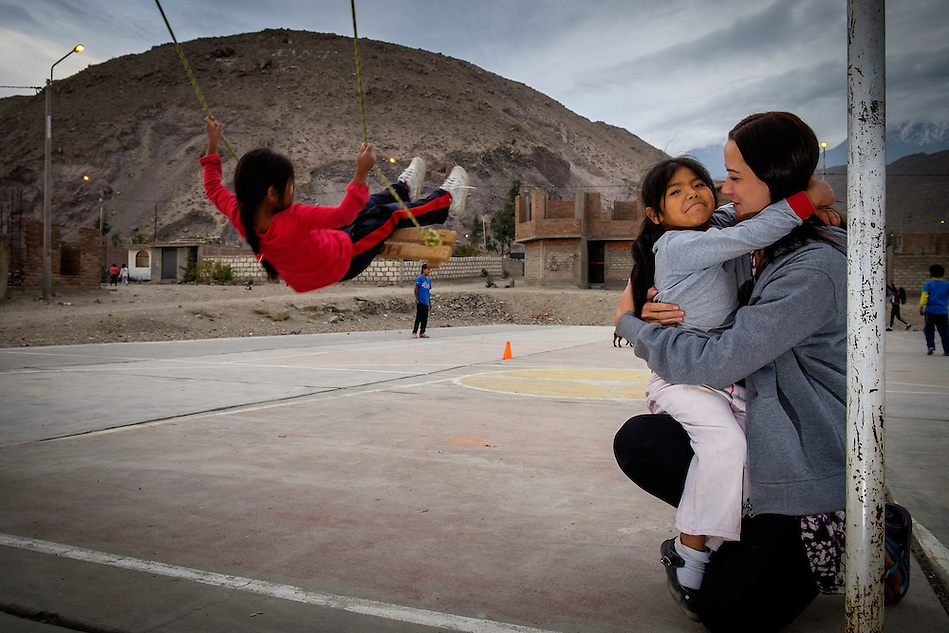 AREQUIPA, PERU - APRIL 7, 2014: Volunteer embracing with student in the community of Flora Tristan for HOOP Peru. HOOP Peru is a NGO fully committed to breaking the cycle of poverty by empowering the Flora Tristan families through enhancing their education. (Daniel Korzeniewski)