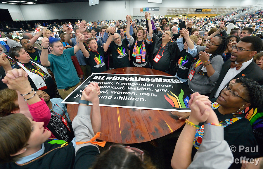 Members of the Black Lives Matter movement disrupt the May 16 proceedings of the 2016 United Methodist General Conference in Portland, Ore. The demonstrators marched into the plenary session chanting slogans and here hold a meeting around the central communion table. Photo by Paul Jeffrey. (Paul Jeffrey)