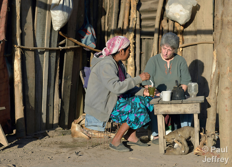 A Wichi indigenous woman, Griselda Arias (left) shares tea with Sister Norma Chiappe, at Arias' home in Lote 75, an indigenous neighborhood of Embarcacion, Argentina. The Wichi in this area, largely traditional hunters and gatherers, have struggled for decades to recover land that has been systematically stolen from them by cattleraisers and large agricultural plantations. Chiappe is a member of the Franciscan Missionaries of Mary who lives in Lote 75. (Paul Jeffrey)