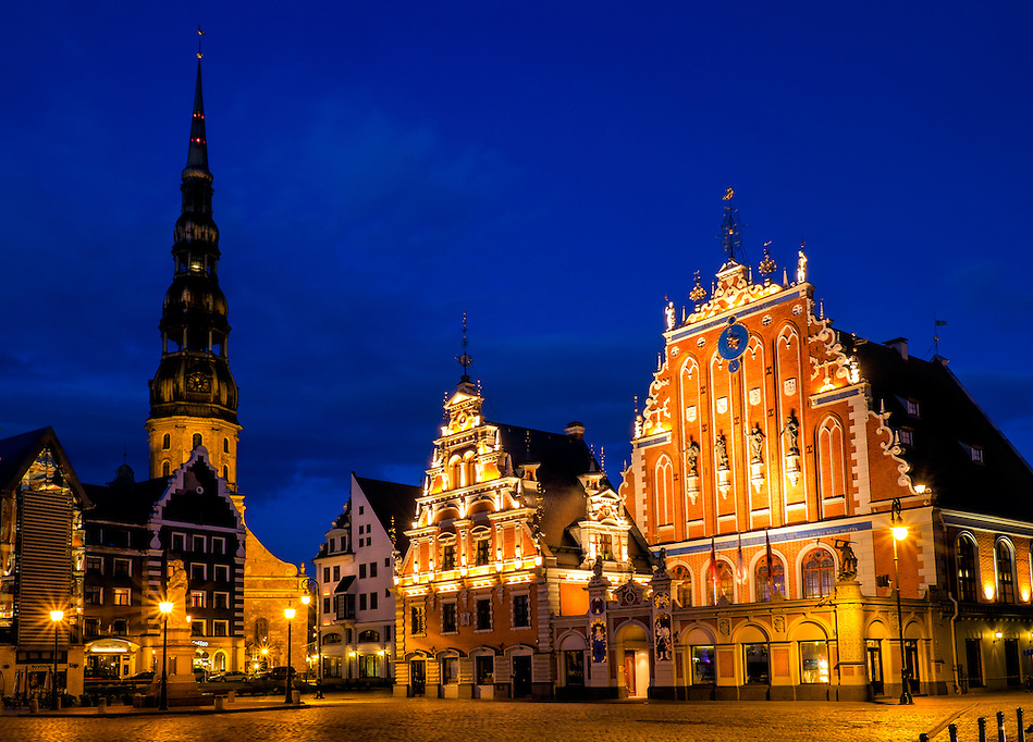 "RIGA, LATVIA - CIRCA MAY 2014: Night view of the Town Square Hall  with ""The House of Blackheads"" and St. Peter's Church in old town Riga at night. (Daniel Korzeniewski)"