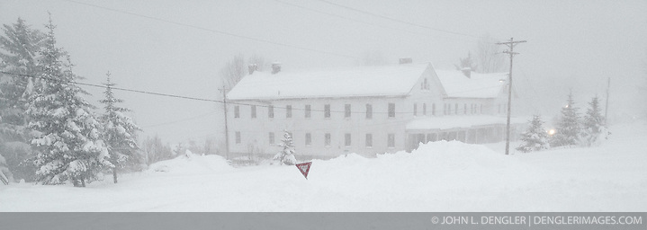 A snow drift loom in this scene from the porch of the Alaska Guardhouse bed and breakfast located on the grounds of historic Fort Seward in Haines, Alaska after an early November blizzard. In the background is one of the fort's former army barracks. SPECIAL NOTE: iPhone photo (John L. Dengler)