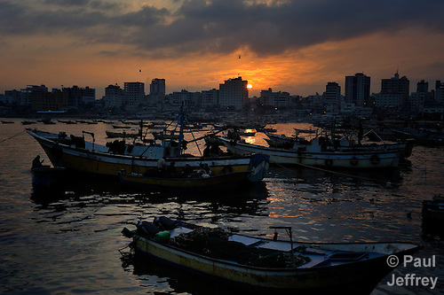 Fishing boats at sunrise in the Gaza City harbor. Under the 1993 Oslo Peace Accords, the people of Gaza were allowed to fish out to 20 nautical miles from their coastline, yet since the Israeli military imposed a naval blockade in 2007 they have been limited to just three nautical miles. In practice, fishers who venture beyond two nautical miles are shot at by Israeli gunboats; several have been injured and some killed. Despite having 40 kilometers of coastline and a long tradition as fishers, many fishers are unemployed and the people of Gaza are forced to import fish from Israel. And what fishing they can do close to shore mostly involves the harvest of immature fish, which biologists warn has a negative impact on fish stocks in the region....