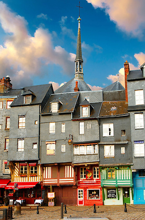 Harbour sided shops with an older couple looking in the window with arms around each other. Honfleur, Normandy, France. (By Travel photographer Paul Williams. http://www.funkystockstockphotos.com)